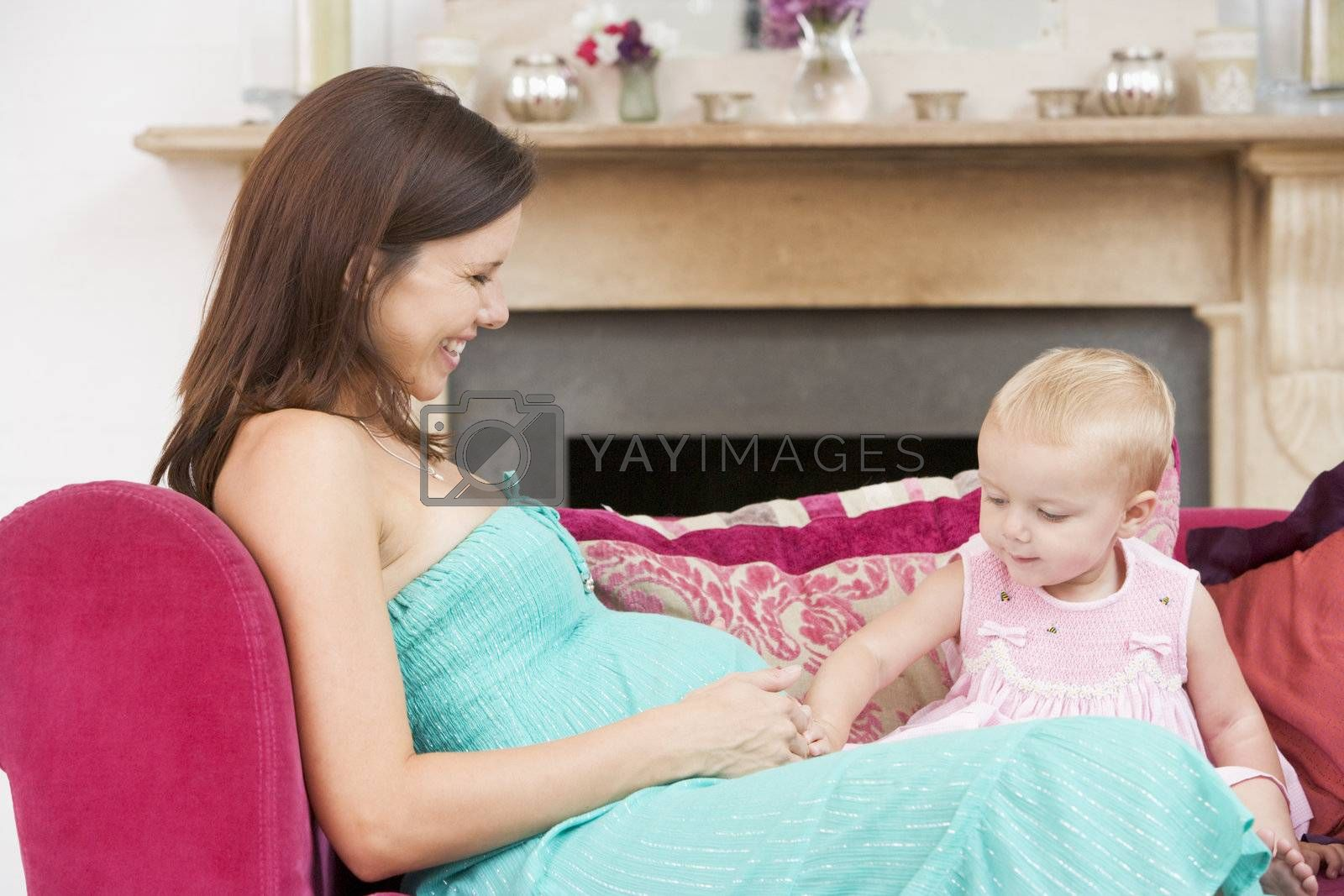 Pregnant mother with daughter in living room touching belly