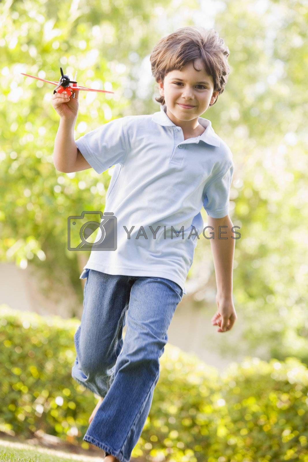 Young boy with toy airplane running outdoors smiling by MonkeyBusiness