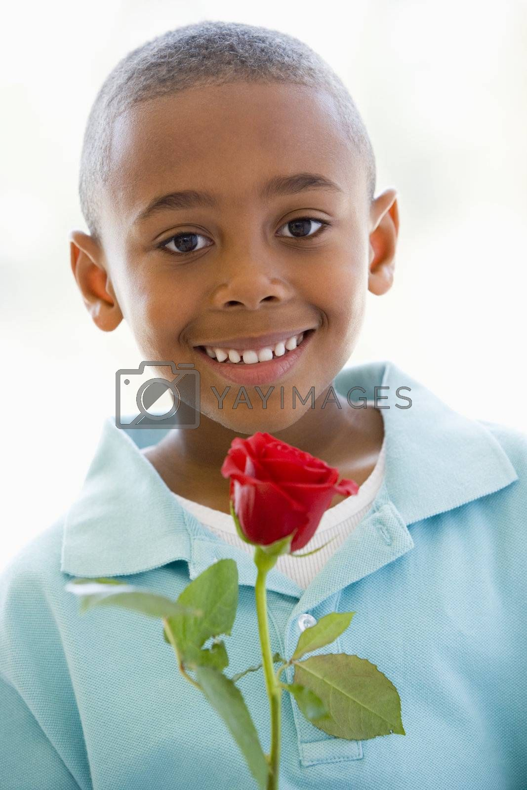 Young boy holding rose smiling