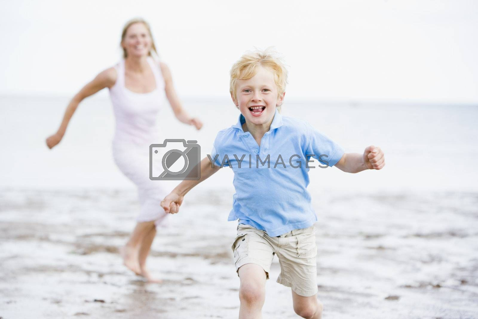 Mother and son running on beach smiling by MonkeyBusiness
