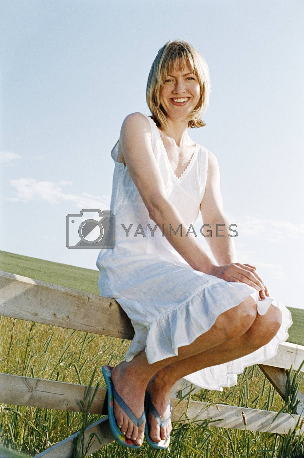 Woman sitting on fence outdoors smiling by MonkeyBusiness