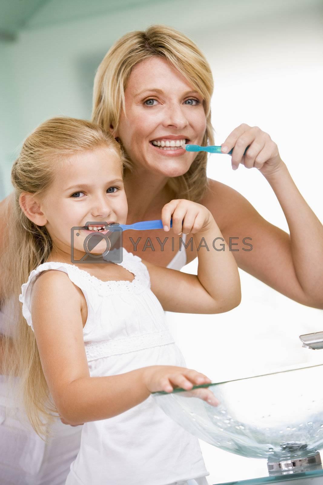 Woman and young girl in bathroom brushing teeth