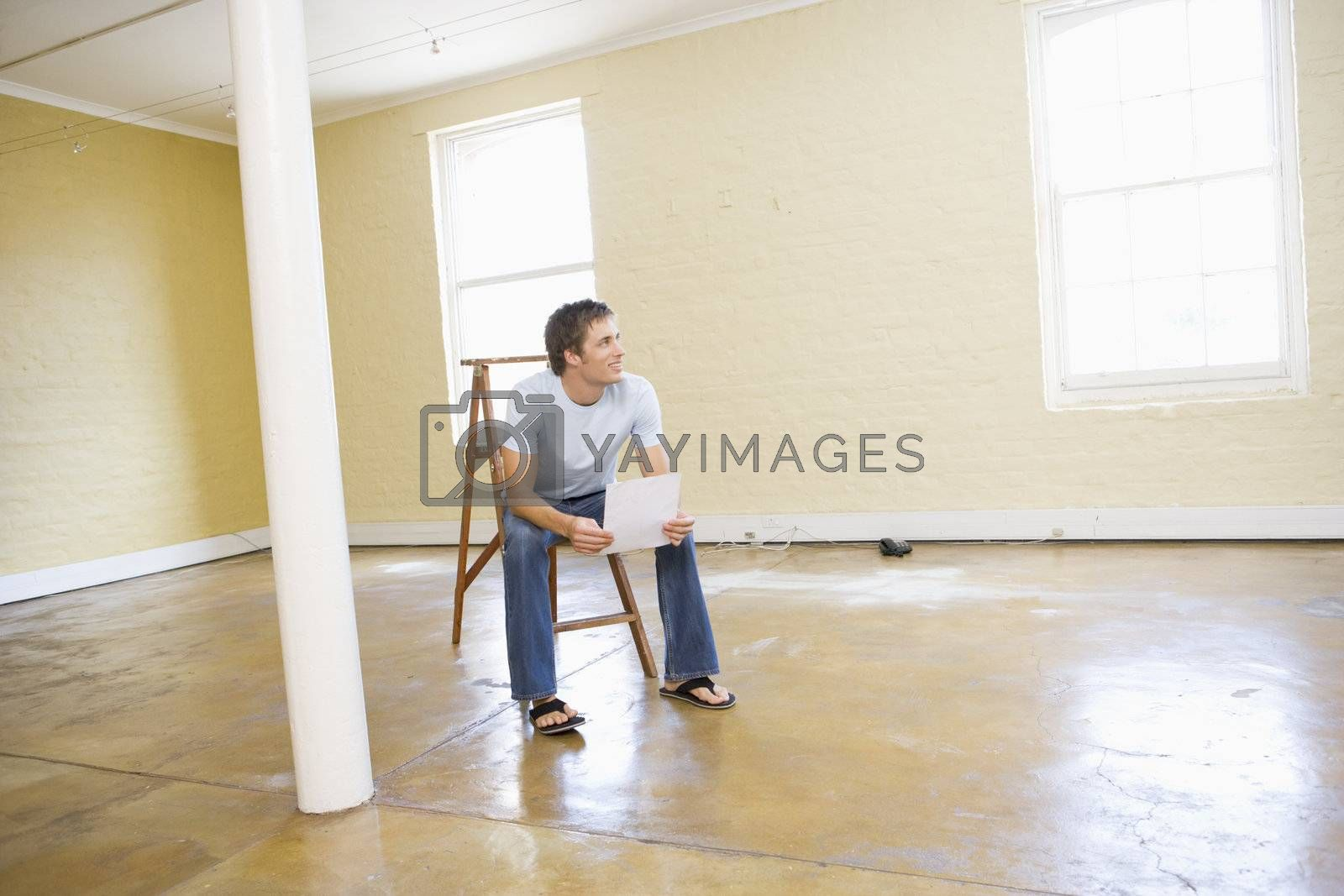 Man sitting on ladder in empty space holding paper smiling by MonkeyBusiness