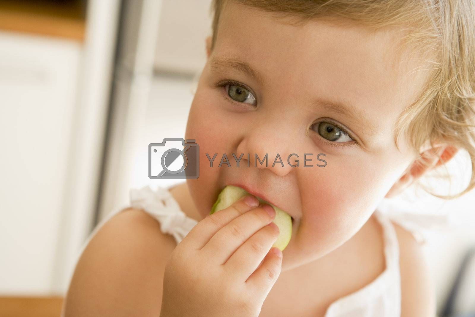 Young girl eating apple indoors by MonkeyBusiness