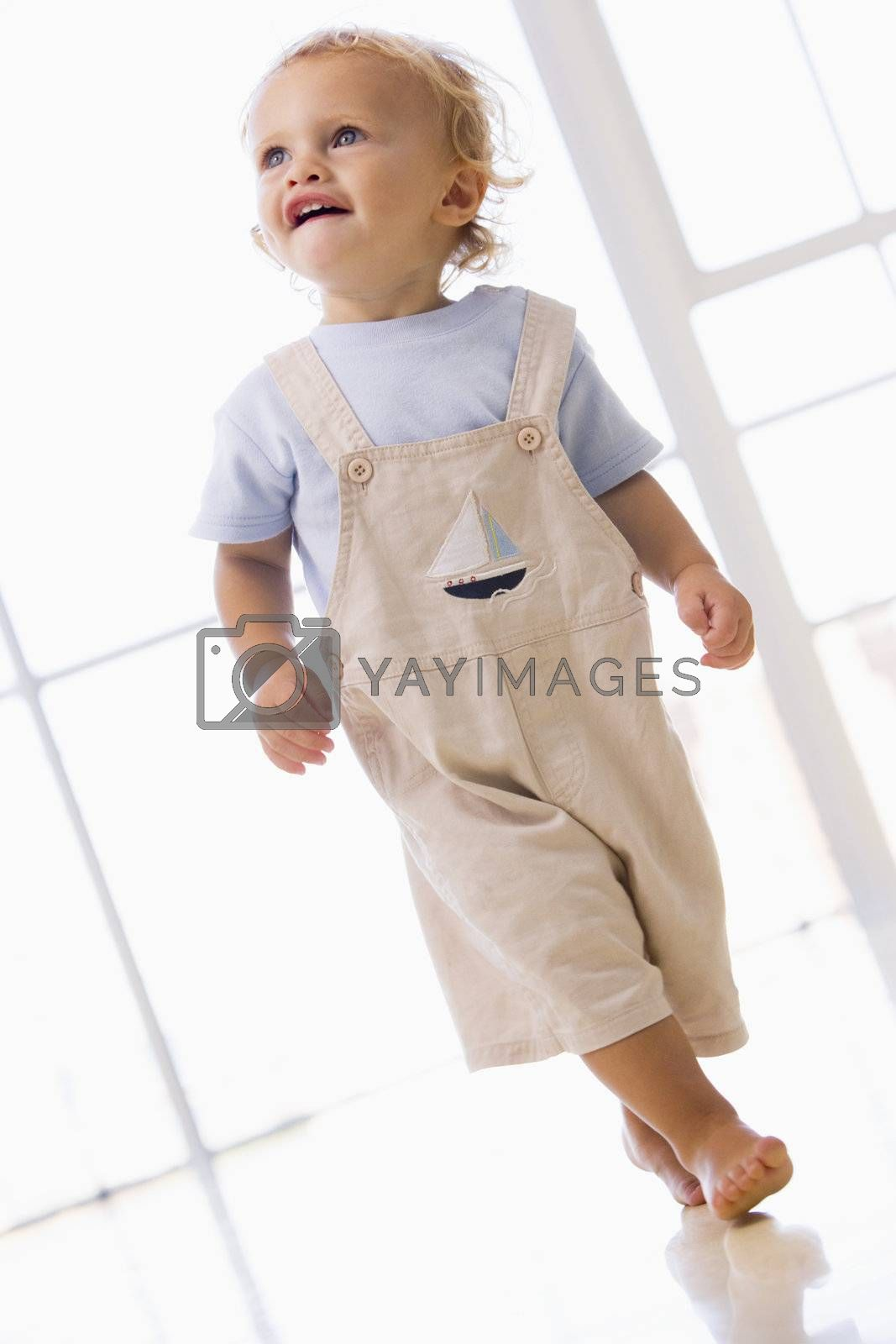 Young boy walking indoors smiling