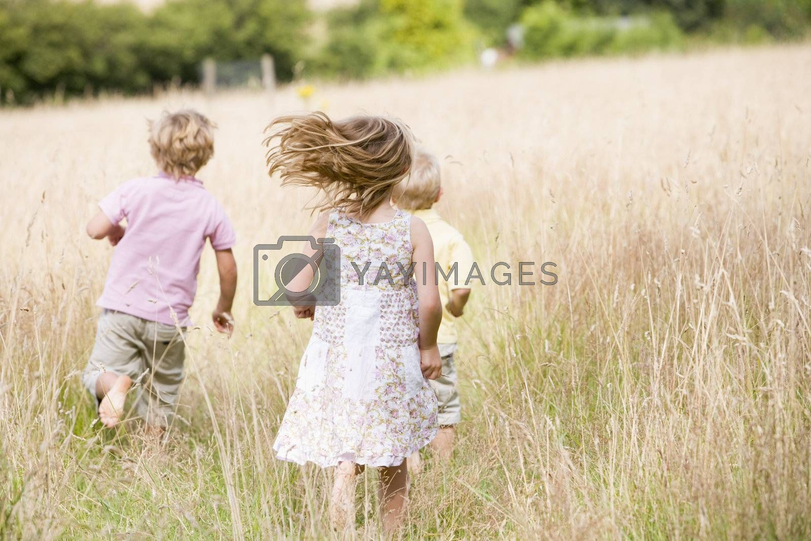 Three young children running outdoors by MonkeyBusiness