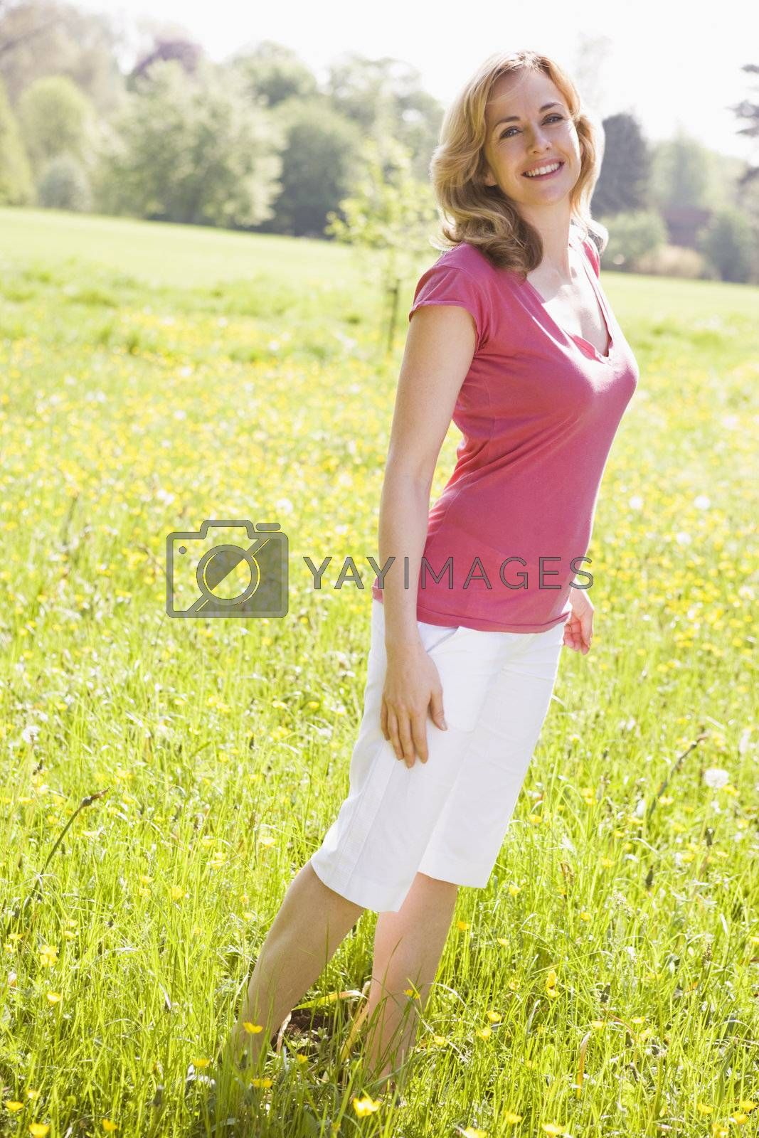 Woman standing outdoors smiling by MonkeyBusiness