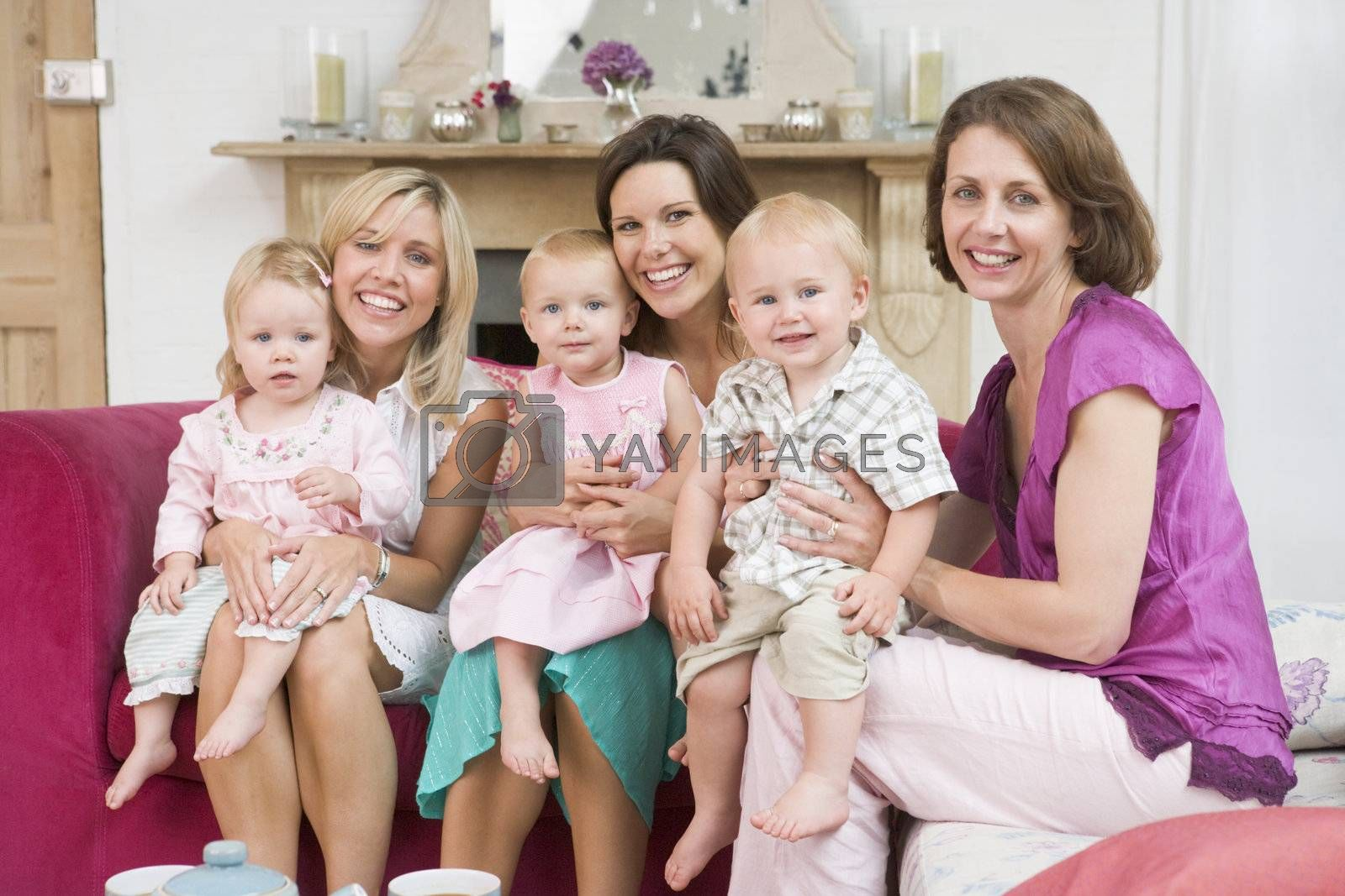 Royalty free image of Three mothers in living room with babies smiling by MonkeyBusiness