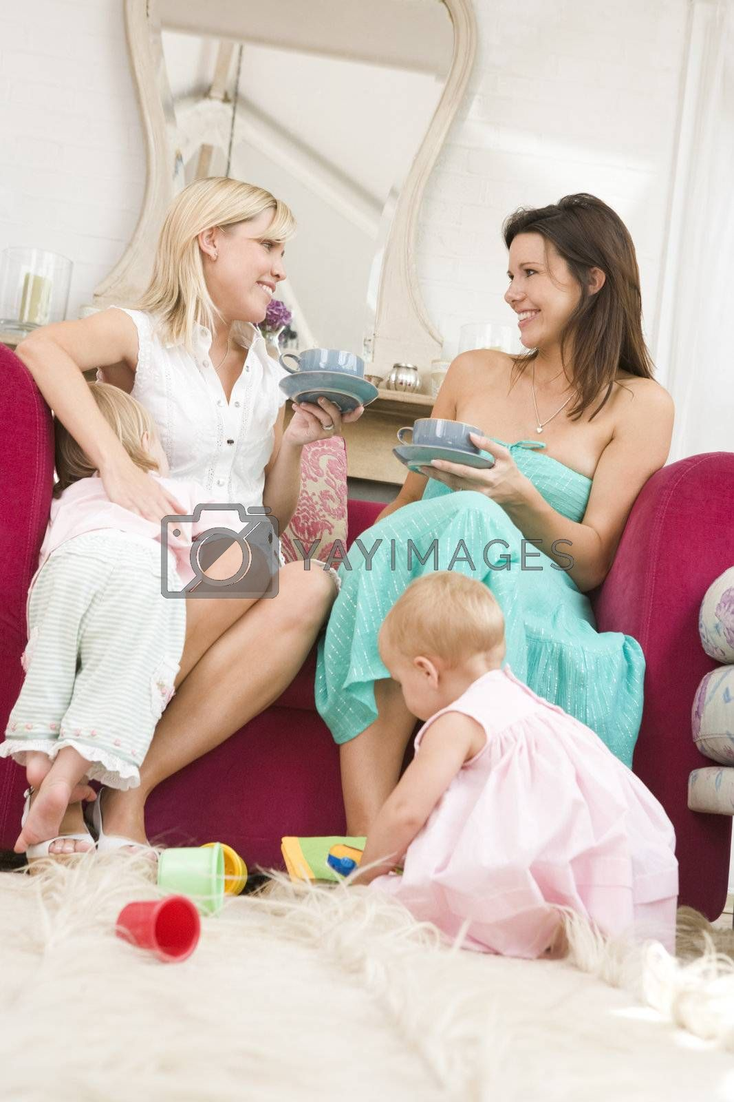 Two mothers in living room with babies and coffee smiling