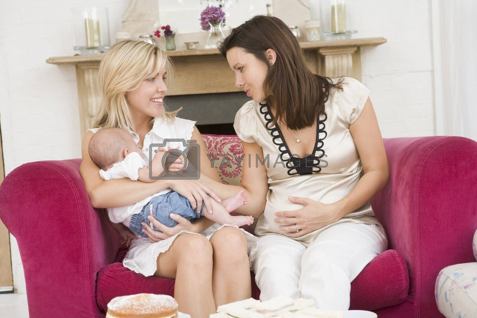 Two mothers in living room with baby and cake