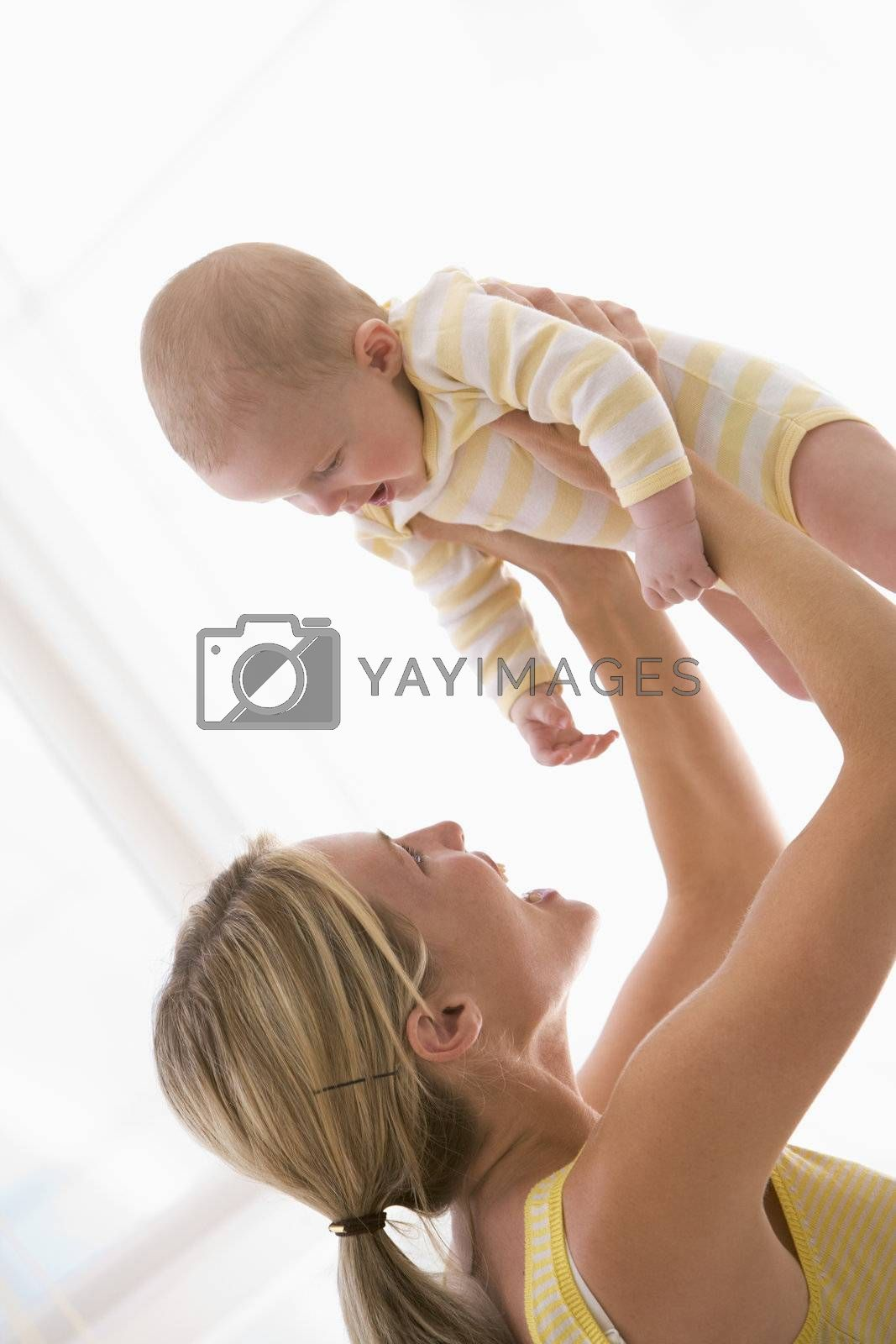 Mother holding baby indoors smiling