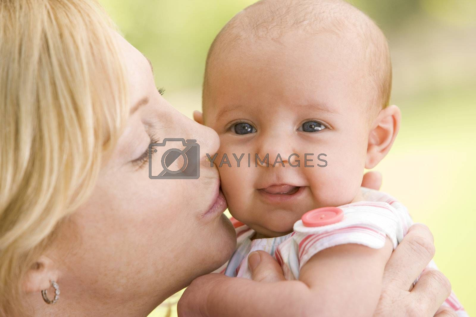 Mother kissing baby outdoors