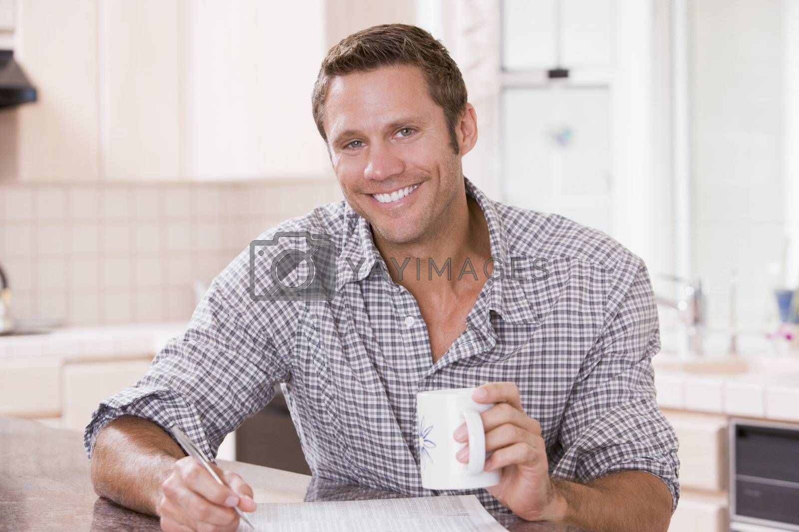 Man in kitchen reading newspaper and smiling by MonkeyBusiness