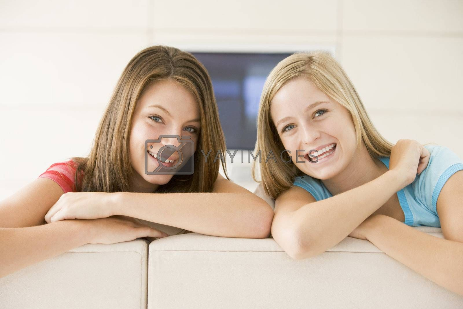 Two women in living room smiling by MonkeyBusiness