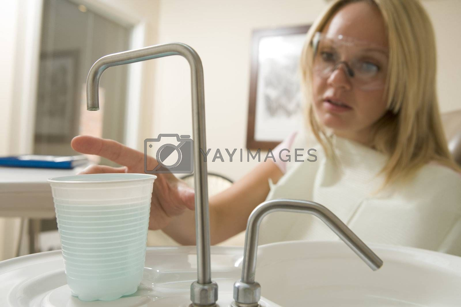Woman in dental exam room reaching for water