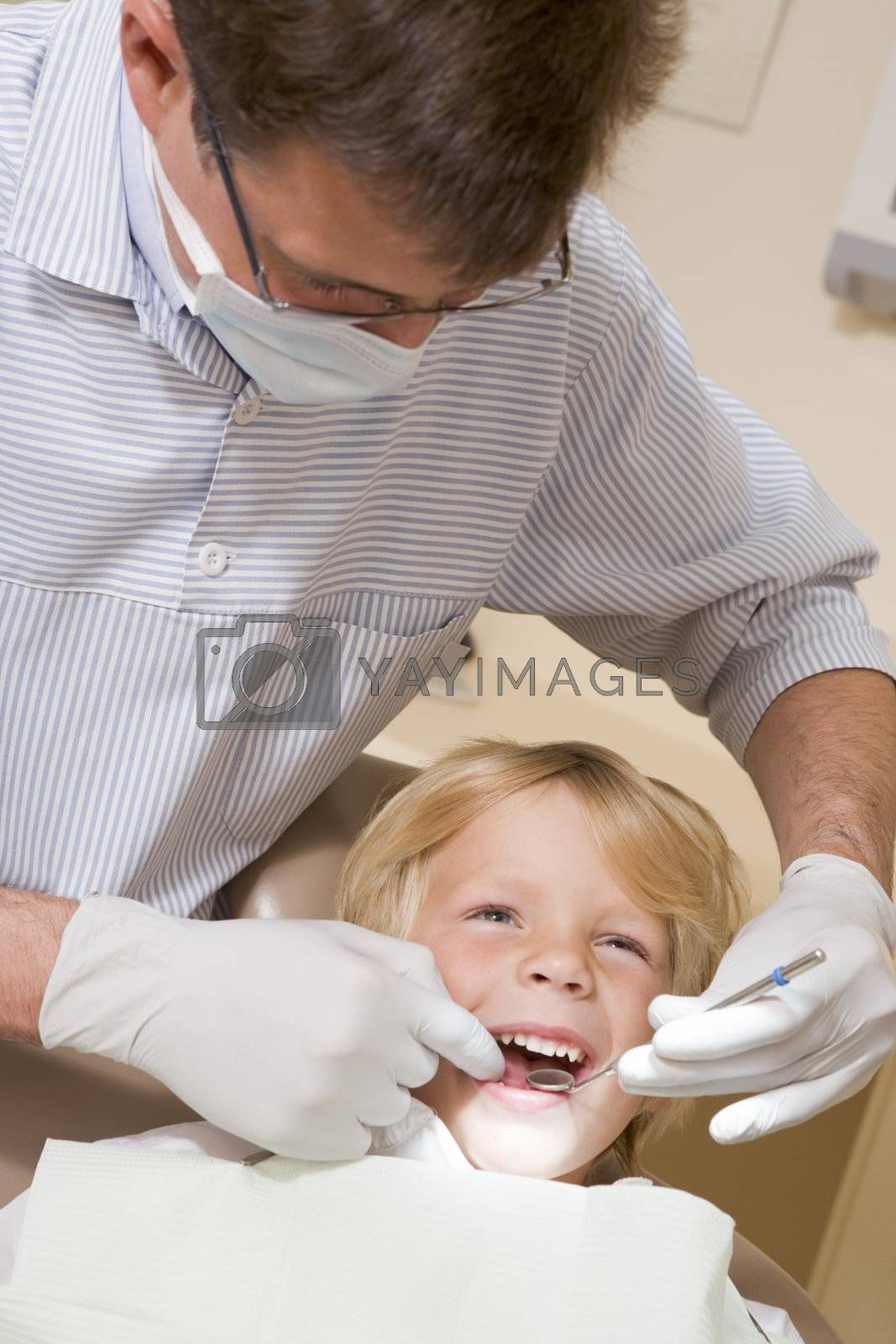 Dentist in exam room with young boy in chair