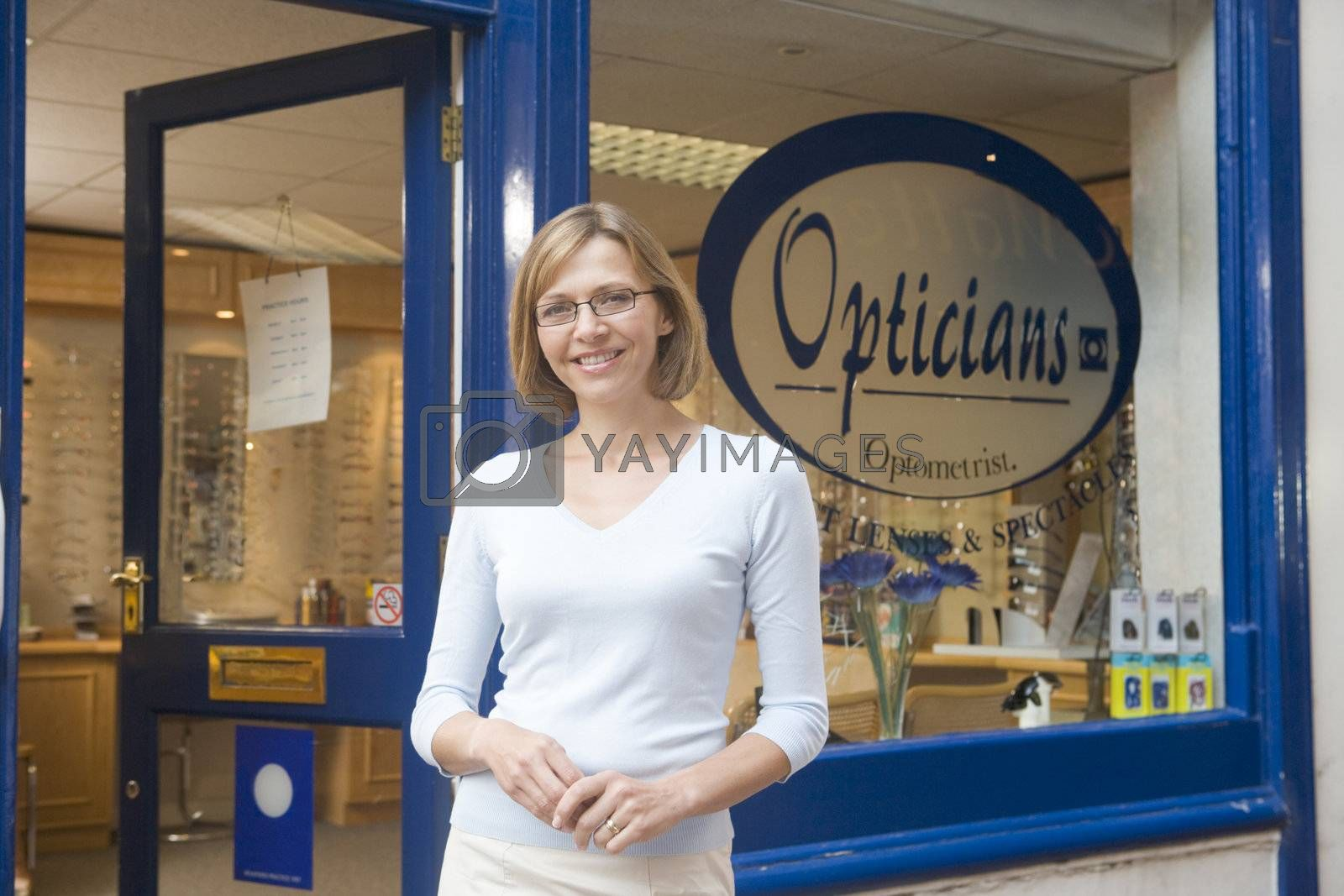 Woman standing at front entrance of optometrists smiling