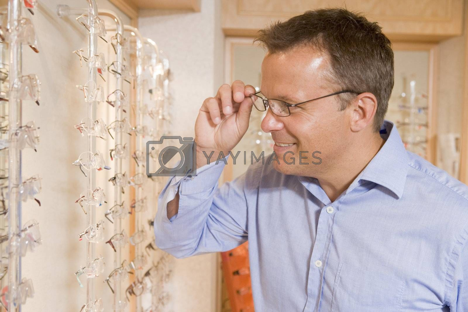 Man trying on eyeglasses at optometrists smiling