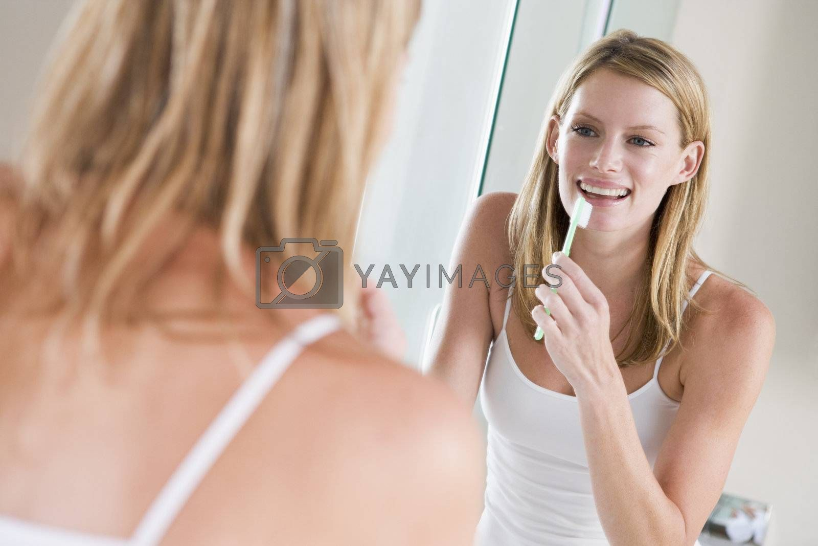 Woman in bathroom brushing teeth smiling