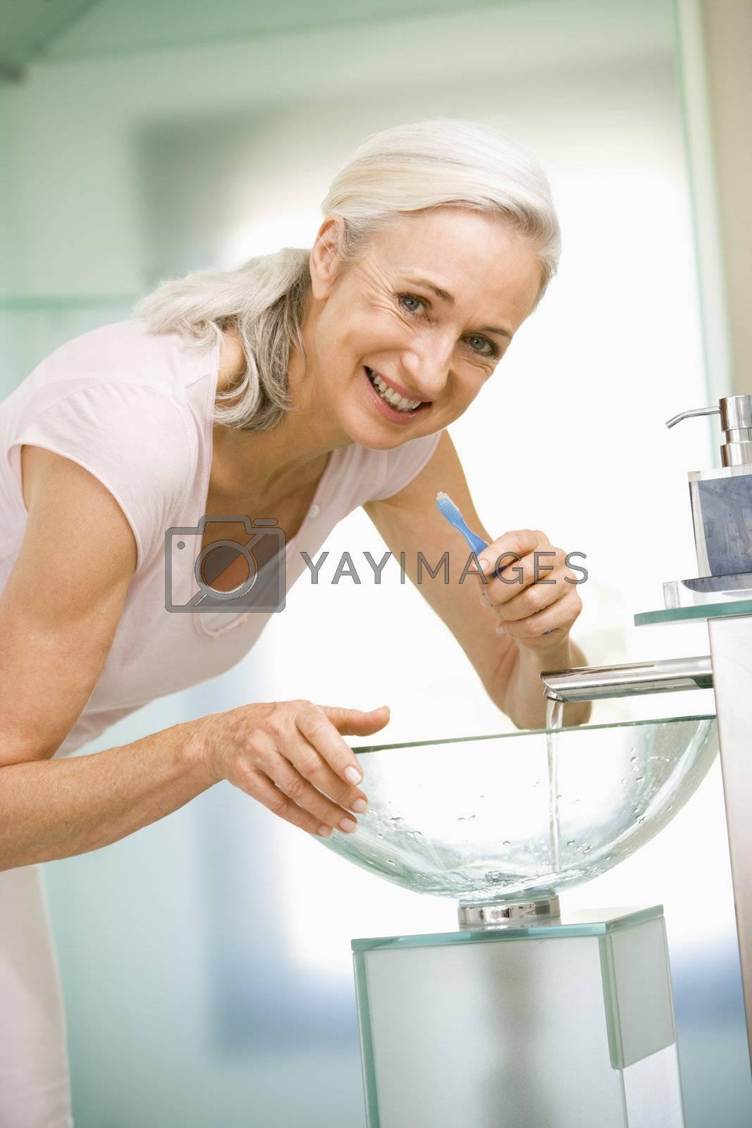 Woman in bathroom brushing teeth smiling