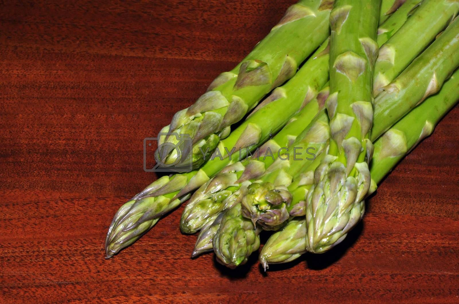 some asparagus on a table of dark wood