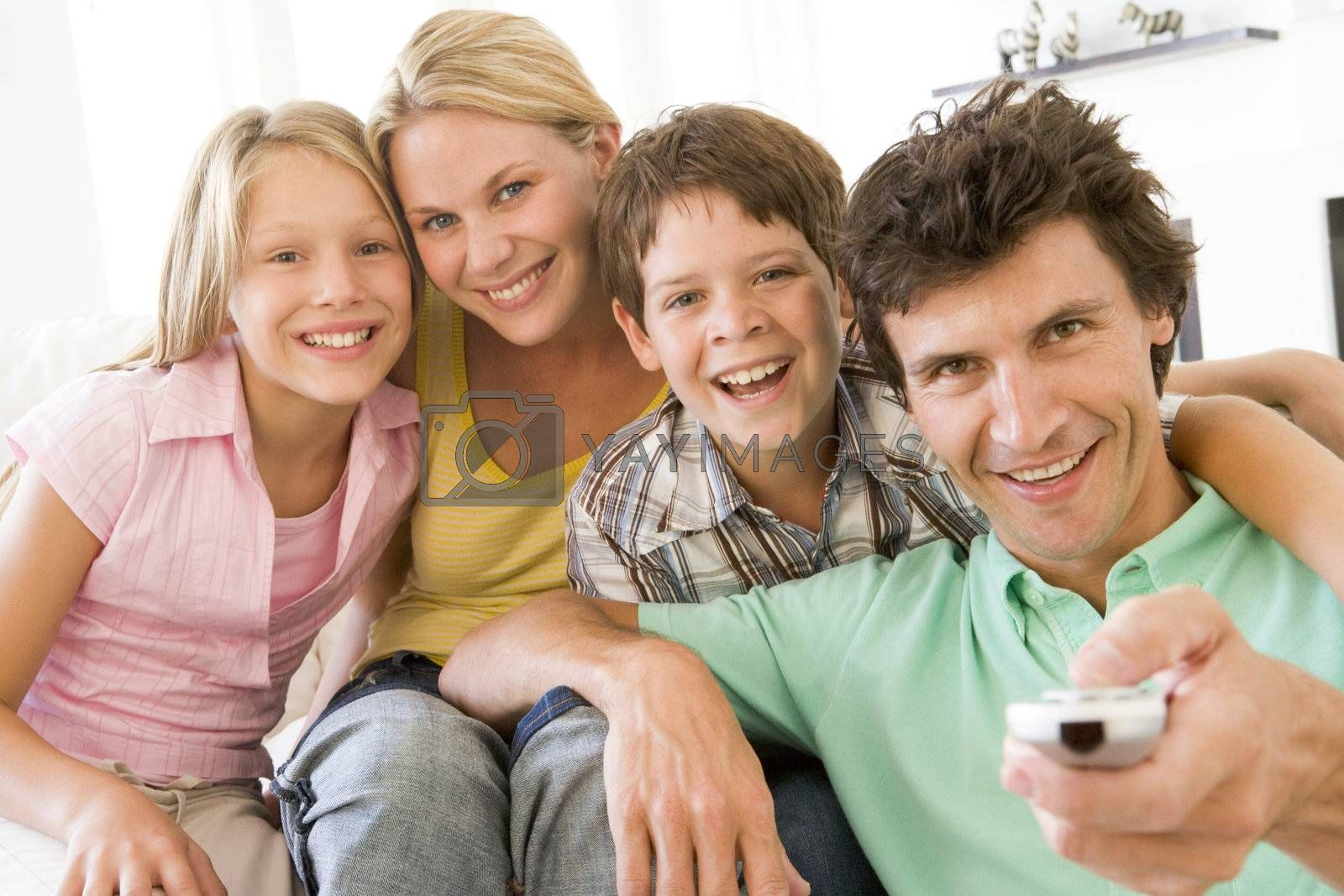Family in living room with remote control smiling by MonkeyBusiness