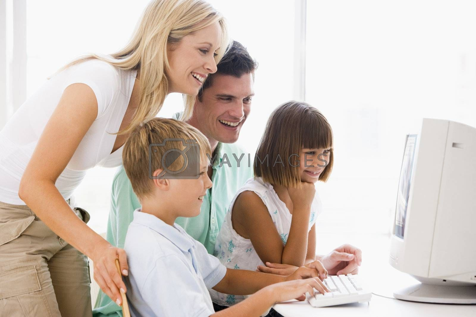 Family in home office using computer smiling by MonkeyBusiness