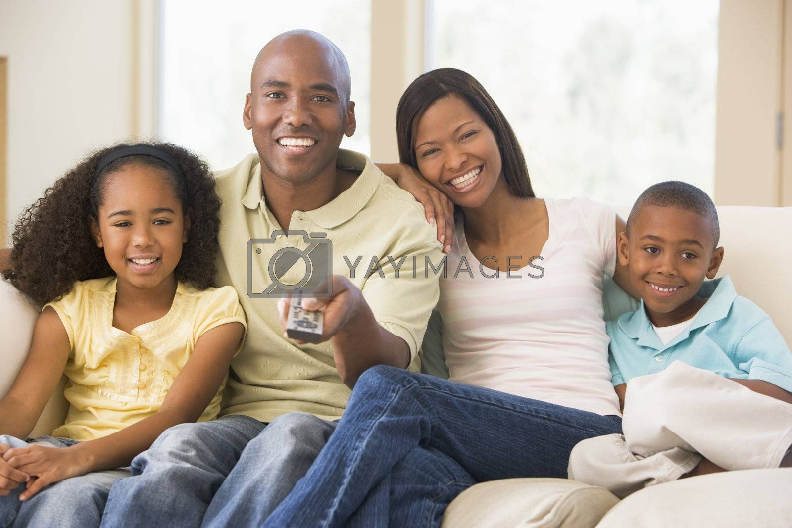 Family sitting in living room with remote control smiling by MonkeyBusiness