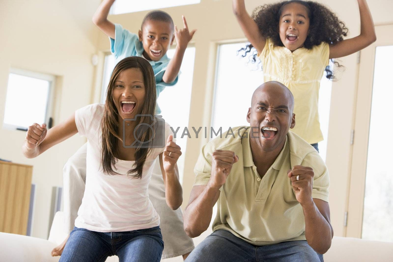 Family in living room cheering and smiling by MonkeyBusiness