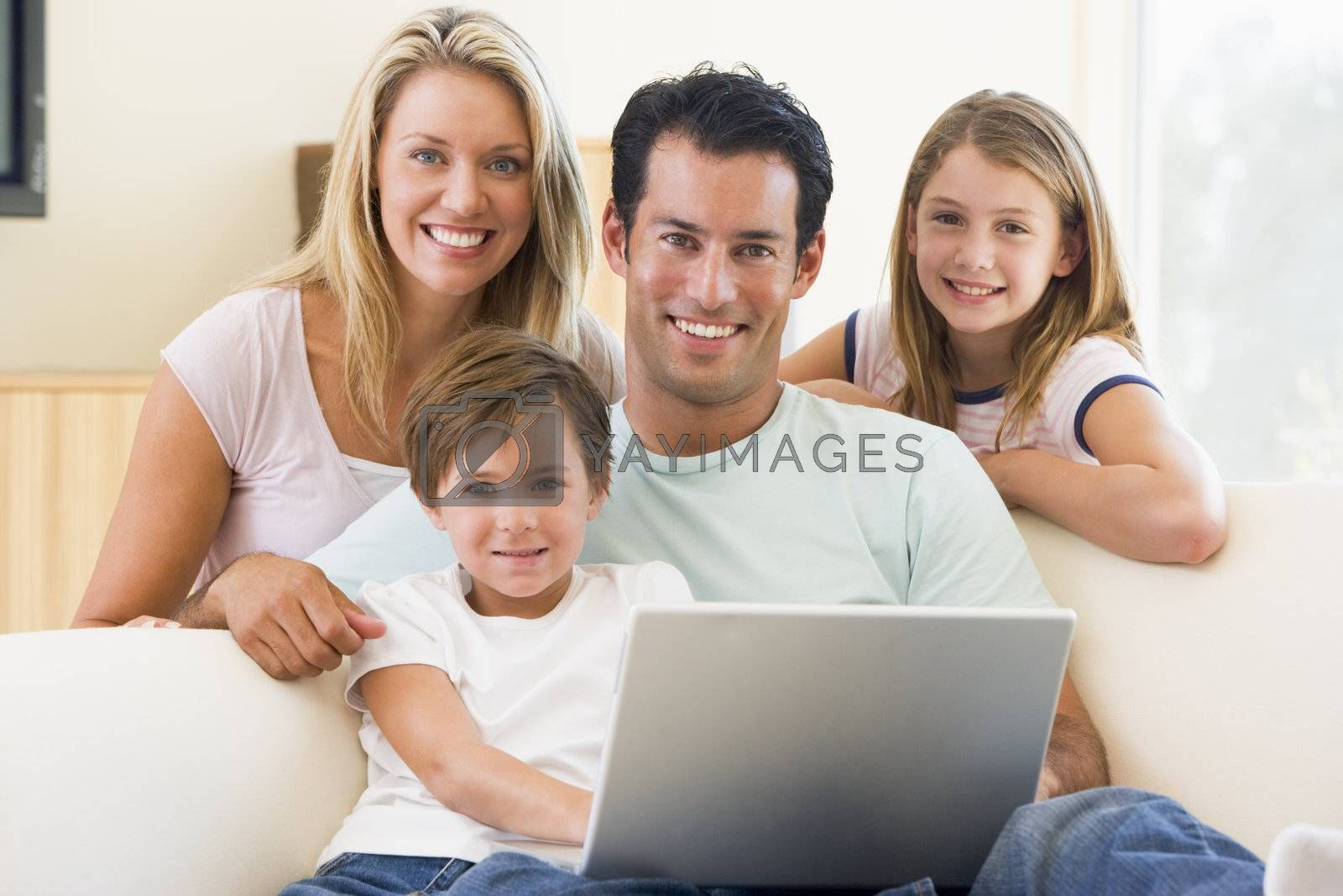 Family in living room with laptop smiling by MonkeyBusiness