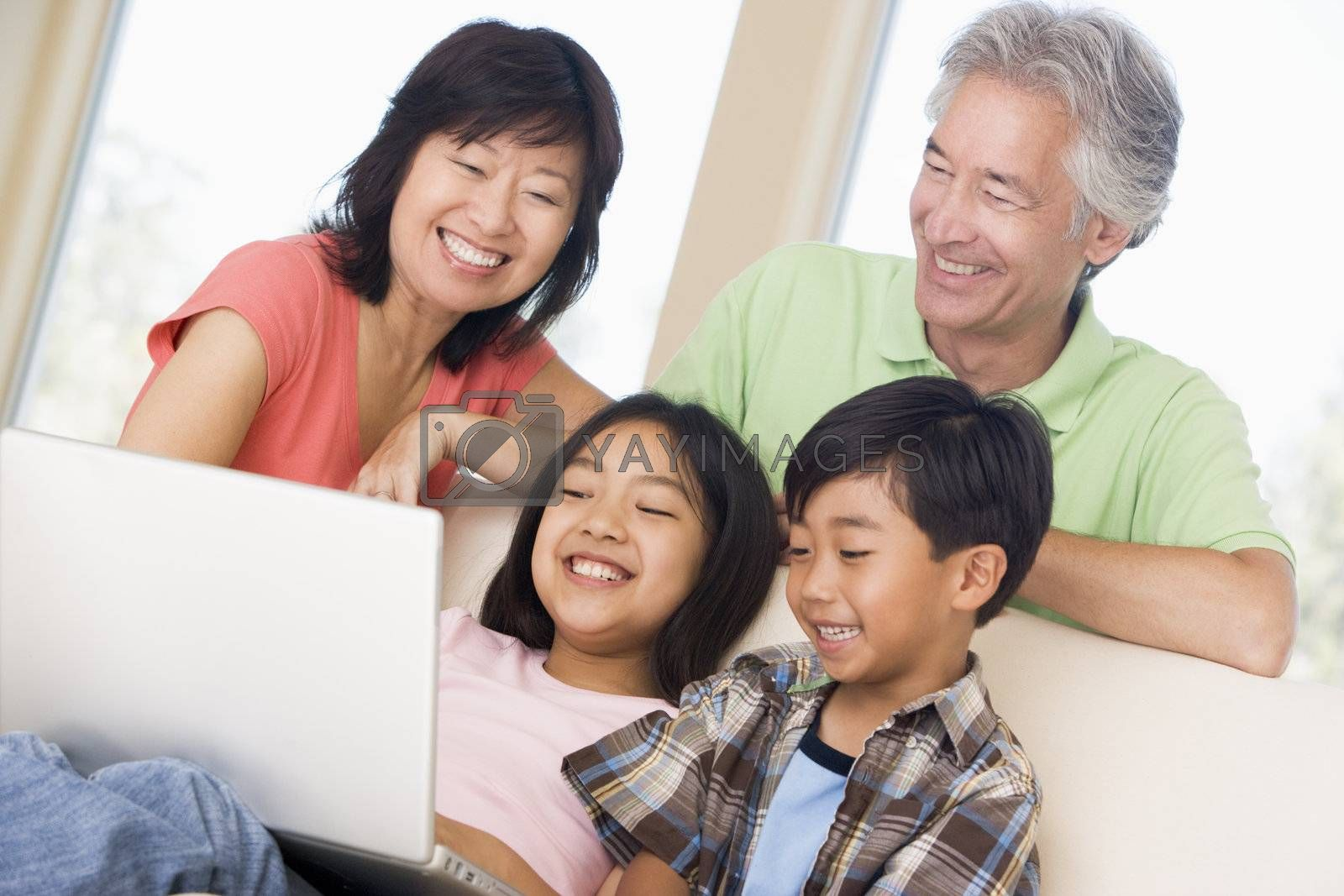 Couple with two young children in living room with laptop smilin by MonkeyBusiness