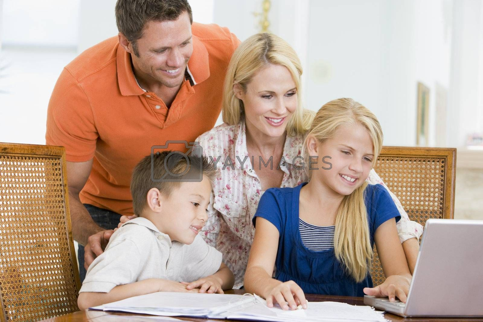 Couple helping two young children with laptop do homework