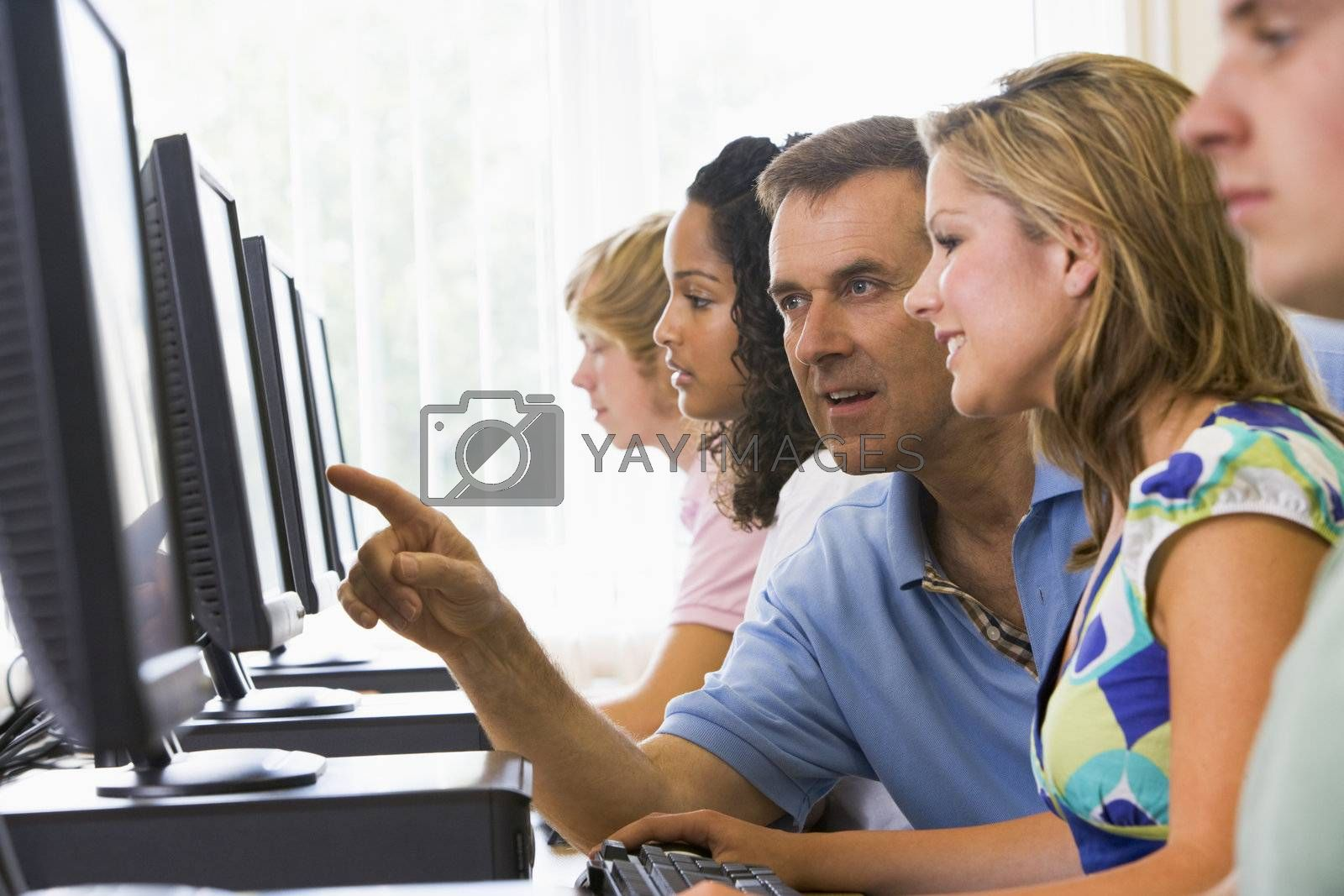 Teacher assisting college student in a computer lab by MonkeyBusiness