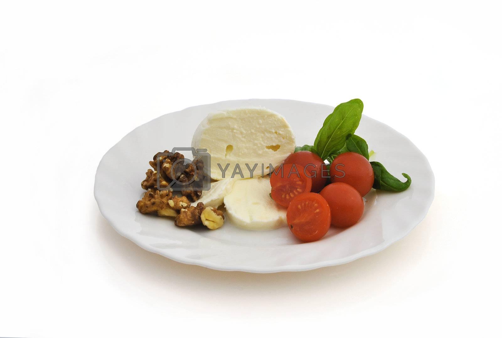 Mozzarella cherry tomatoes and walnuts on white background