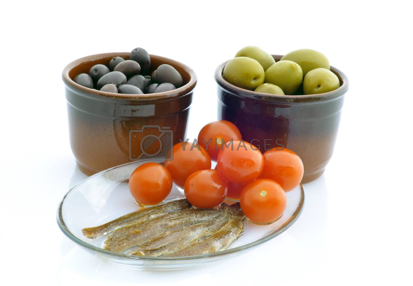 Green and black olives, tomatoes and anchovies on white backgrounds