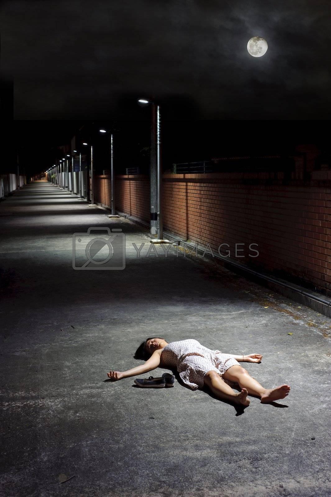 Female lies dead in the street under a night sky