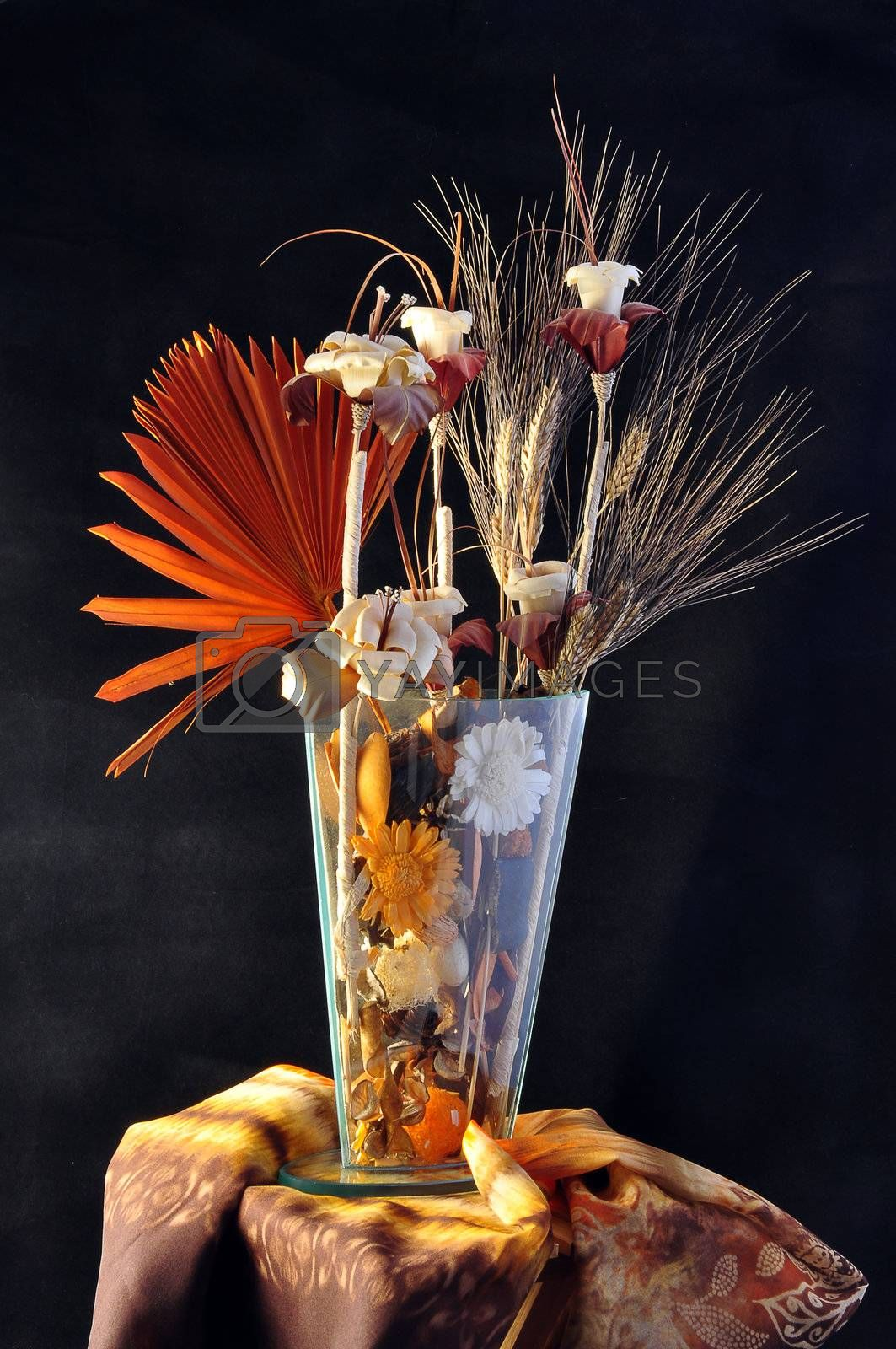 Composition of flowers in wood and Iin crystal vase on a black background