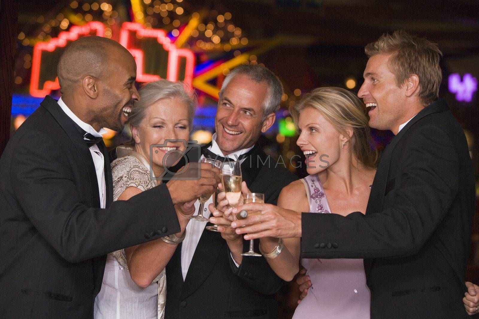 Five people in casino with champagne smiling