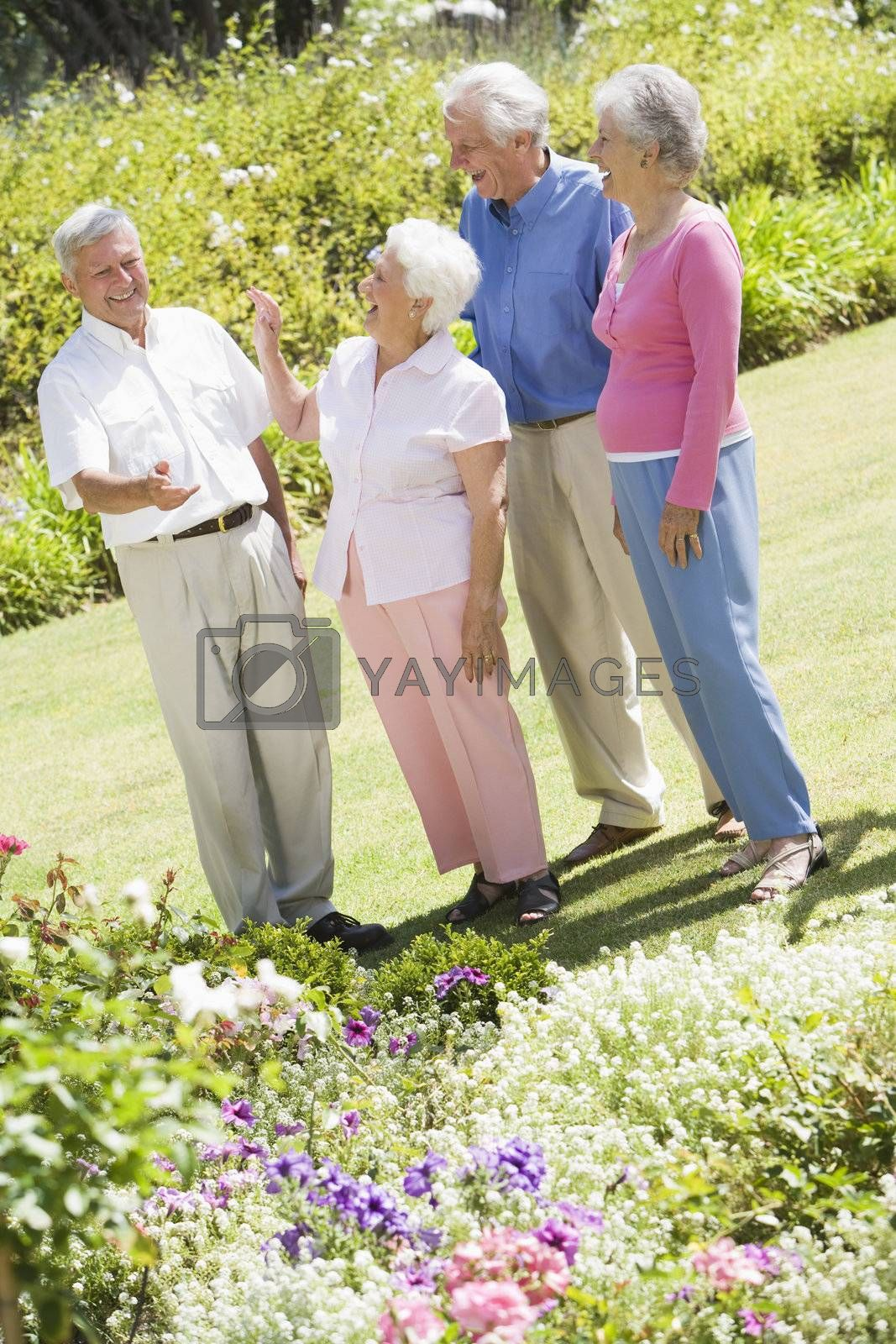 Group of senior friends in garden admiring flowerbeds