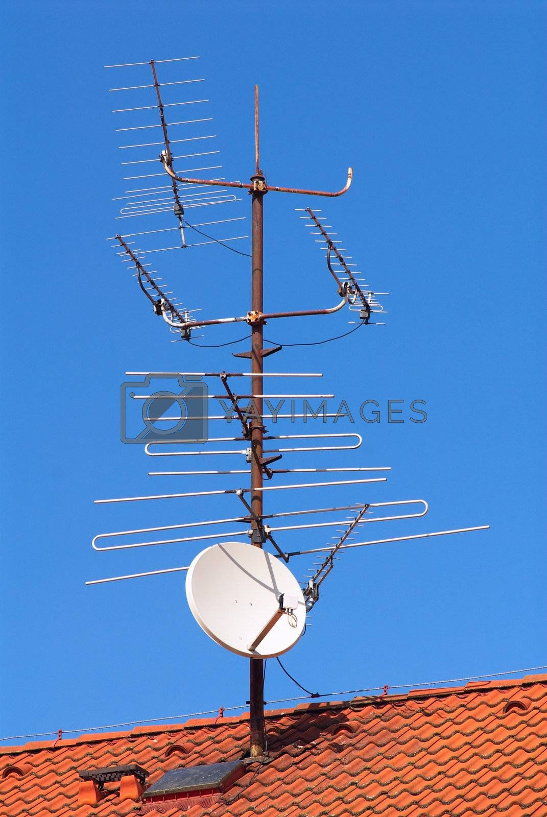 Photo of a roof of the suburban house with the attached aerials of communication
