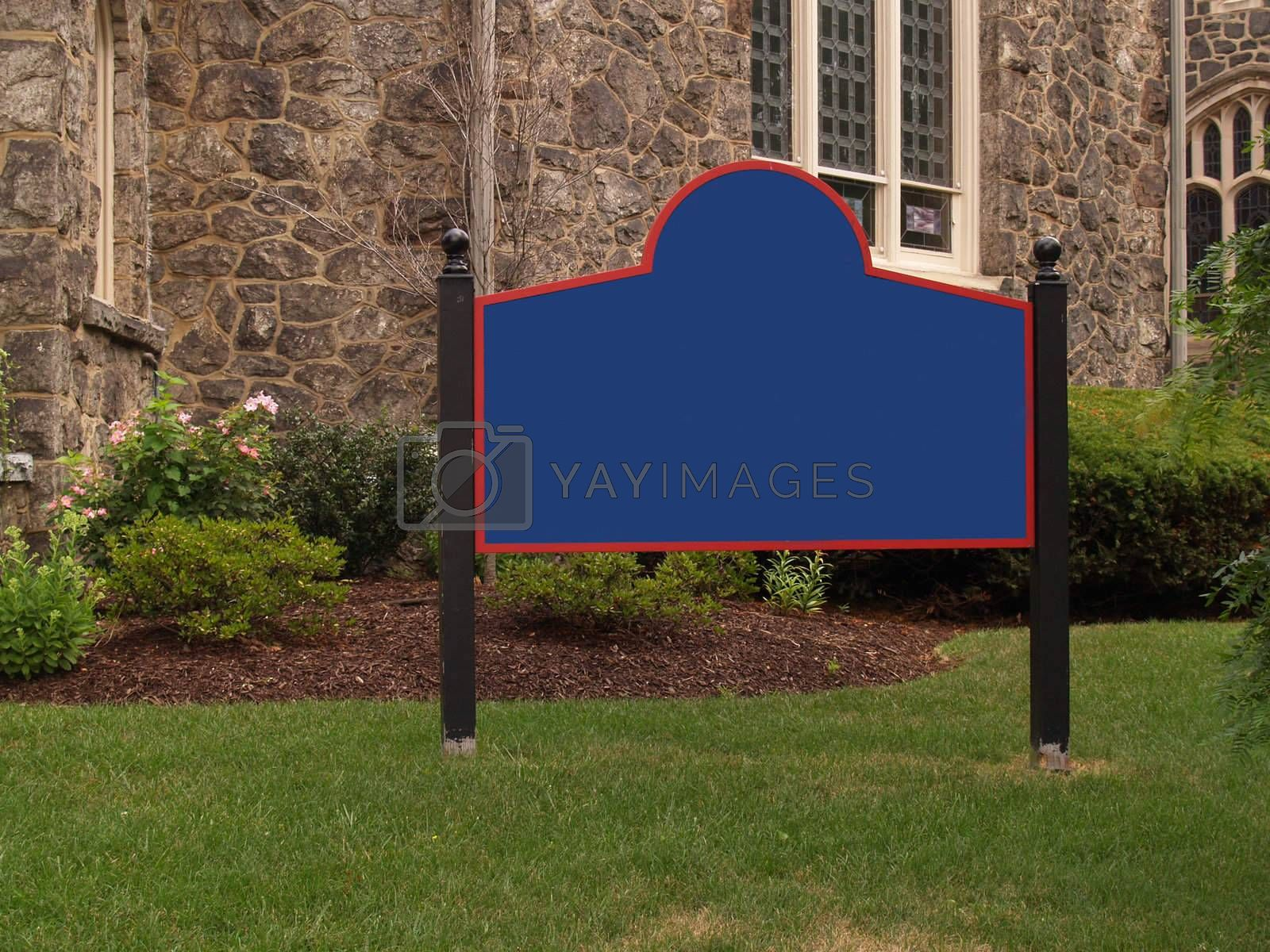 blank sign by a stone church and grass lawn
