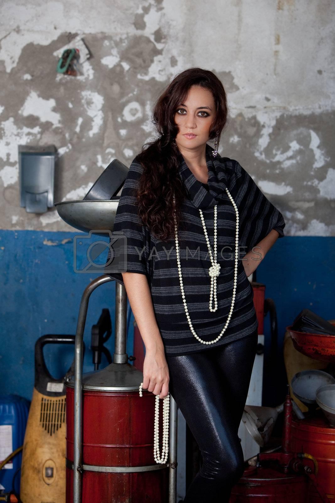 A young brazilian female model shot in a dirty auto repair shop.