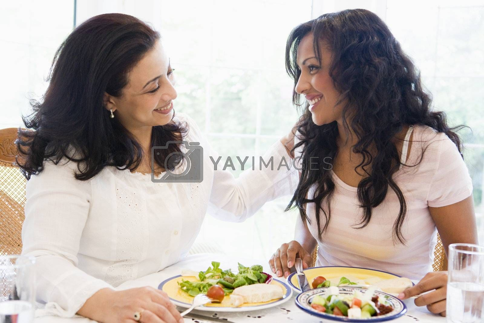Two women sitting at dinner table smiling (high key)