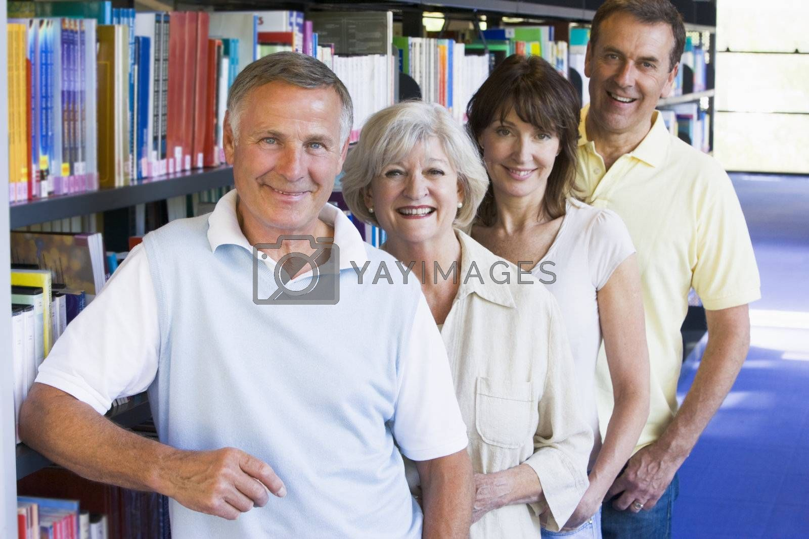 Four people in library standing by bookshelves