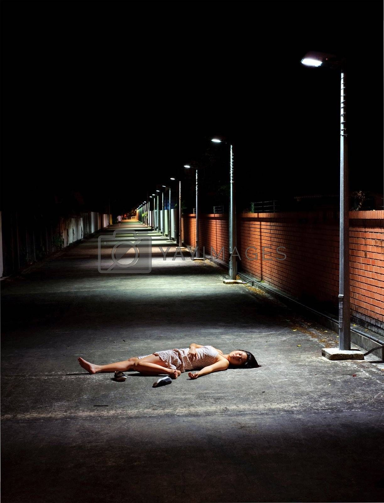 Girl lies vulnerable in the street