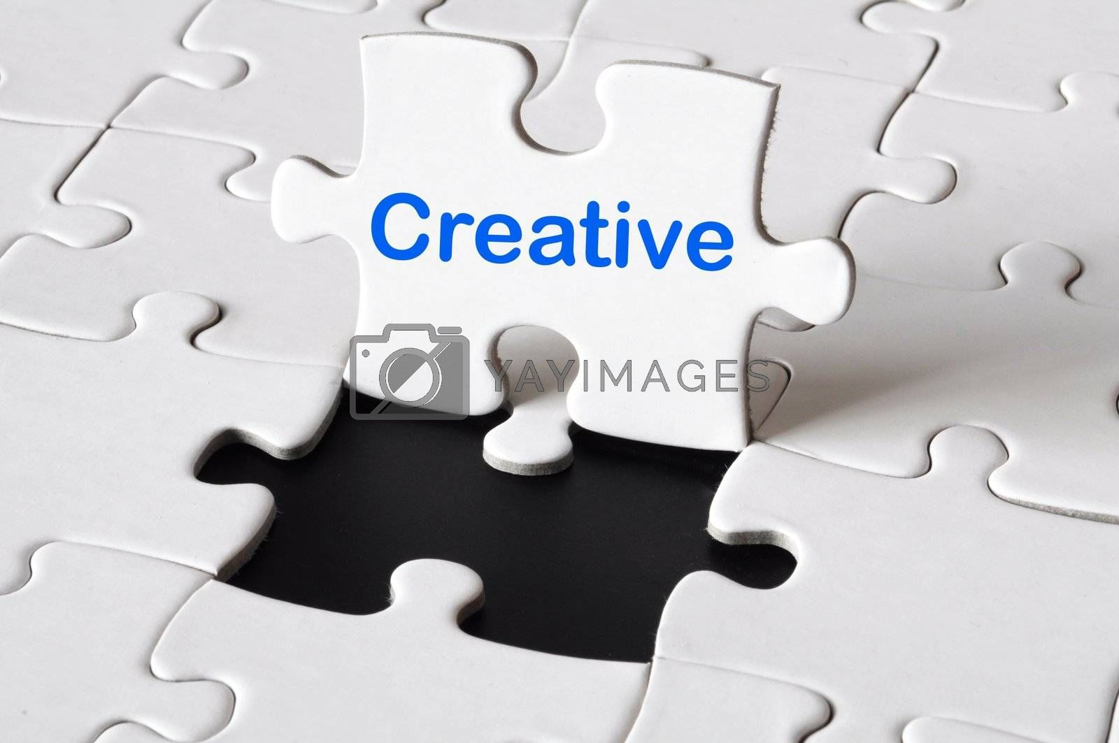 creativity concept with white puzzle and blue text