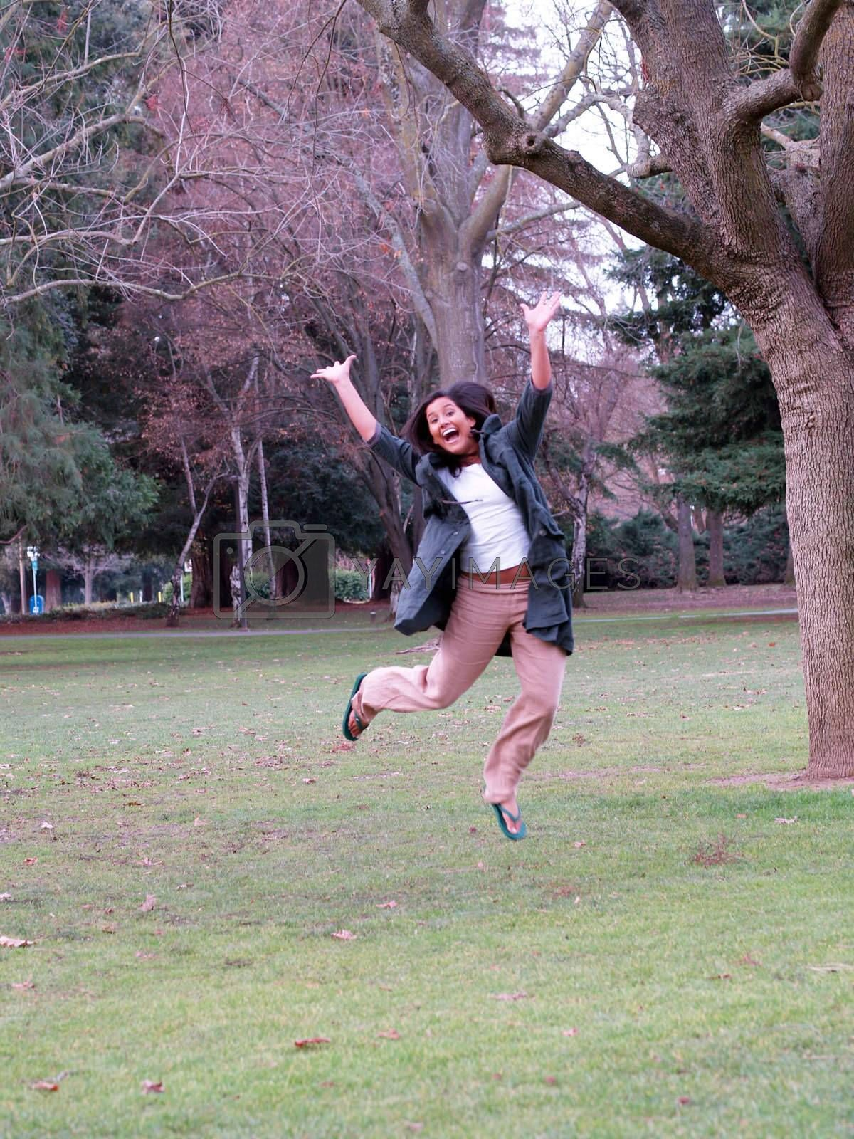 Smiling jump with arms up amid trees and grass