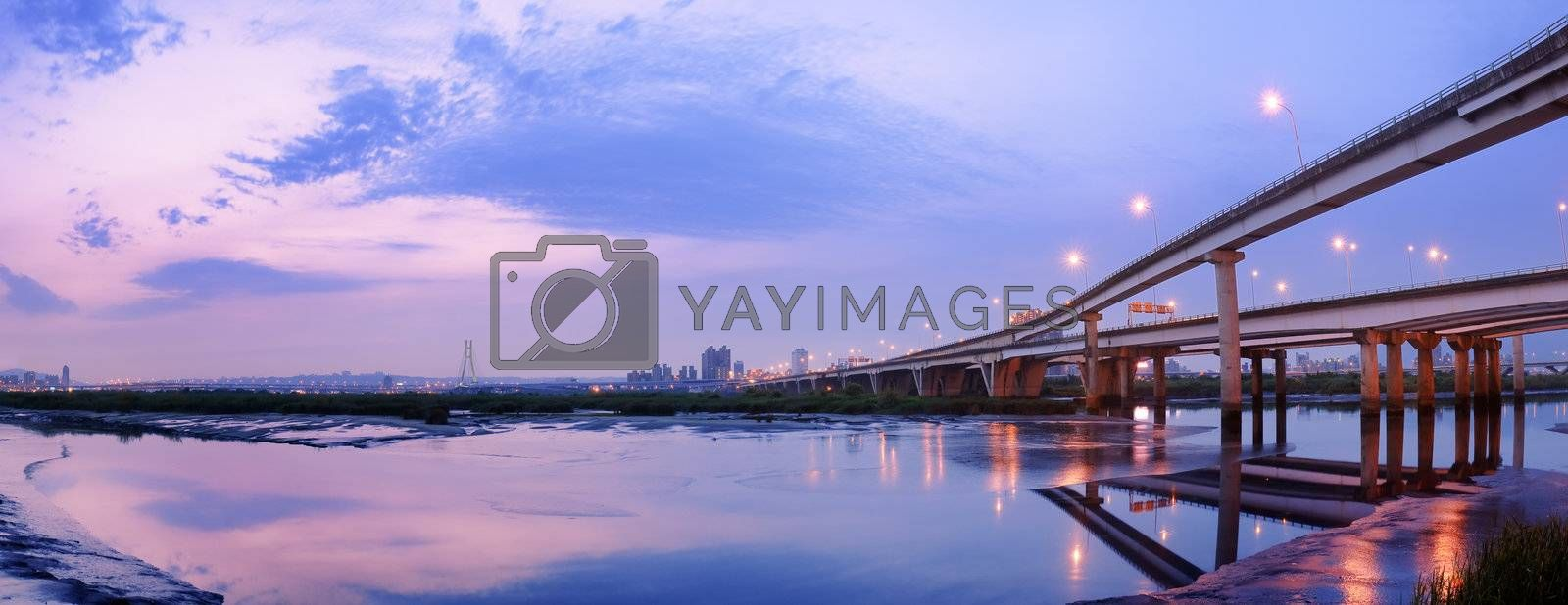 Panoramic cityscape with modern building and bridge under dramatic sky and illuminated reflection on sand and water of river in Taipei, Taiwan.