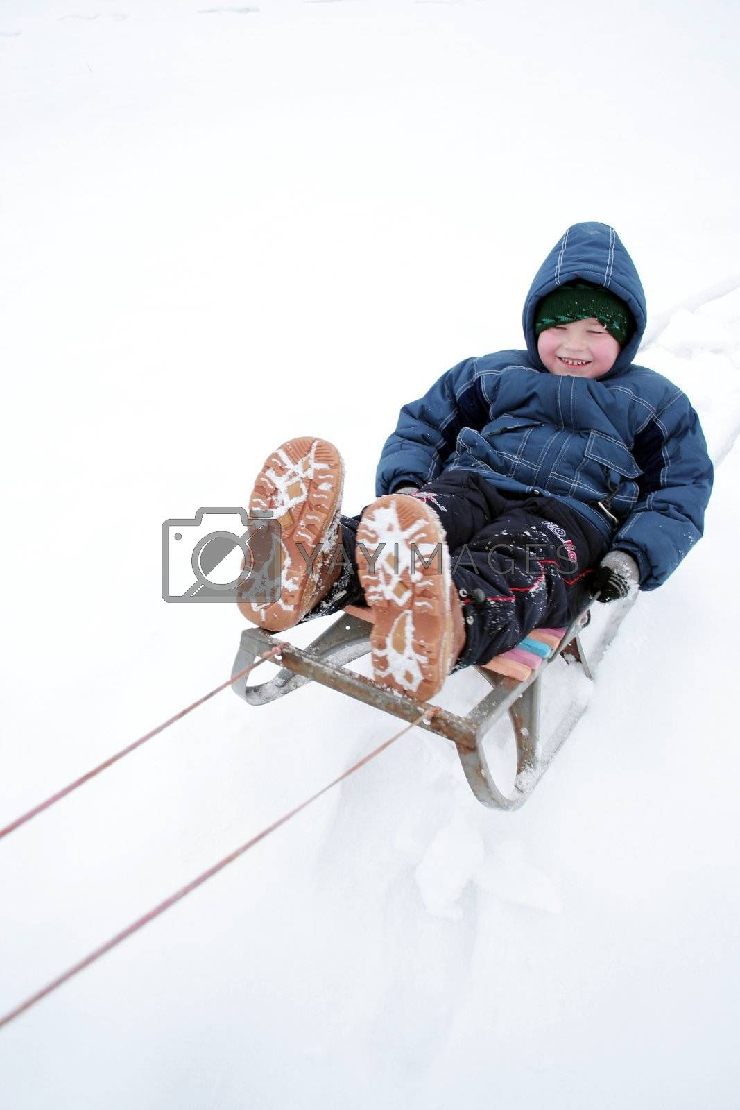 Winter riding of the boy on sled