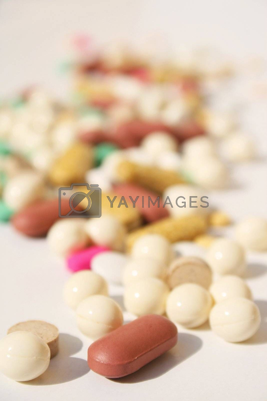 Various pills against white background with shallow depth of field on foreground